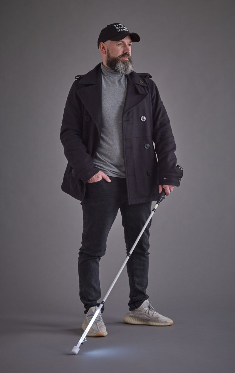 Dave Steele wearing a jacket with his right hand tucked into his pant while holding an LED mobility cane in his left hand.